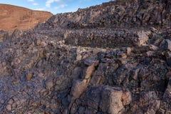 Lavadagzomende aardlagen op de helling van de vulkanische krater van Al Wahbah, Saudi-Arabië stock foto