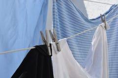 Lavadero limpio que se seca afuera en la cuerda para tender la ropa en la sol fotografía de archivo libre de regalías