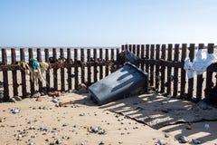 Lavado acima da poluição dos restos da praia Desperdícios na costa de Englan imagem de stock royalty free