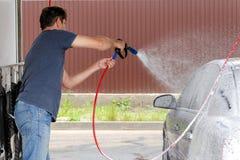Lavado del coche usando el agua de alta presi?n foto de archivo libre de regalías