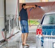 Lavado del coche usando el agua de alta presi?n fotos de archivo libres de regalías