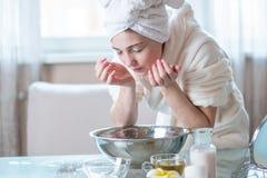 Lavado hermoso de la mujer joven y cara de restauración con agua por la mañana Higiene y cuidado para la piel en casa foto de archivo