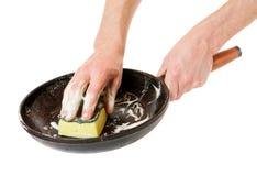 Lavado a mano de los hombres con una cacerola de la esponja Fotos de archivo libres de regalías