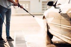 Lavado masculino del trabajador el coche con la lavadora de alta presión imagen de archivo libre de regalías