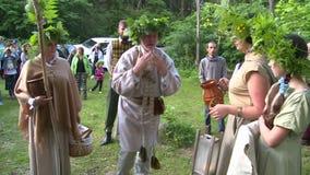 Lavado pagano mayor del sacerdote de la ayuda de la sacerdotisa con agua de la fuente del bosque almacen de metraje de vídeo