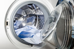 Lavadora cargada con la camisa azul Foto de archivo