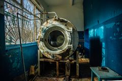 Lavadora industrial rota oxidada vieja con la pintura de la peladura en lavadero en el hospital psiquiátrico abandonado fotos de archivo libres de regalías