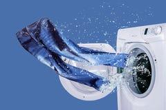 Lavadora y vaqueros recientemente lavados planchados Imágenes de archivo libres de regalías