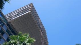 Lavadoras de ventana que cuelgan de cuerdas flojas suspendidas en edificio alto usando los enjugadores para limpiar metrajes