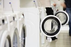 Lavadoras en tienda de dispositivo y comprador defocused Imagen de archivo