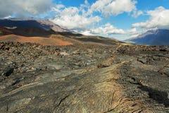 Lavafeld an Tolbachik-Vulkan, nach Eruption im Jahre 2012 auf Hintergrund großem Udina-Vulkan und Vulkan Plosky Tolbachik Stockfoto