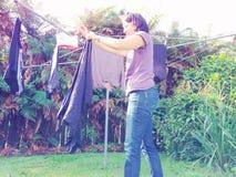 Lavage accrochant de femme au foyer sur la corde à linge rotatoire Image stock