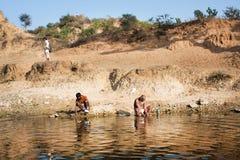 Lavage de matin de pauvres hommes sur la berge Image stock