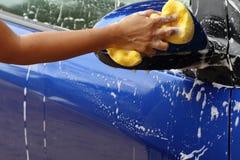 Lavage de voiture extérieur avec l'éponge jaune Image stock