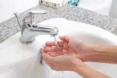 Lavage des mains avec l'eau courante de dessous Image libre de droits