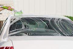 Lavage du toit de la voiture avec la mousse sur la station de lavage Photo libre de droits