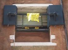Lavage jaune vers le haut des gants et du tissu accrochant hors d'une fenêtre Photographie stock libre de droits