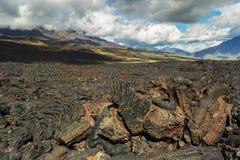 Lavagebied bij Tolbachik-vulkaan, na uitbarsting in 2012 op vulkaan de achtergrond Grote van Udina en de vulkaan van Plosky Tolba Royalty-vrije Stock Foto