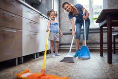 Lavagem da filha da mãe o assoalho em casa Imagem de Stock Royalty Free