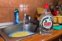 Lavagem da louça feericamente líquida na banca da cozinha, água da torneira de fluxo no fundo imagem de stock