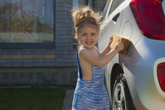 Lavagem da menina um carro Carro limpo de ajuda da família da criança Imagem de Stock Royalty Free