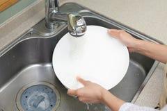 Lavagem da mulher os pratos foto de stock