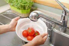 Lavagem da mulher os tomates fotografia de stock