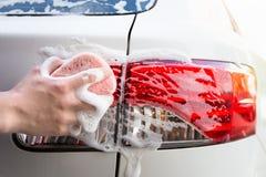 Lavagem de carros do punho - farol de lavagem do carro da mão masculina Imagens de Stock