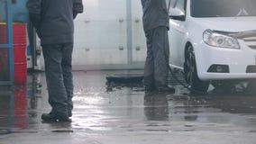Lavagem de carros - o trabalhador no auto serviço está lavando um carro nos Sul por mangueiras da água filme