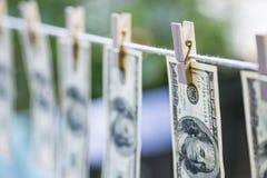 Lavagem de dinheiro Os dólares americanos de lavagem de dinheiro penduraram para fora para secar 100 notas de dólar que penduram  Fotografia de Stock