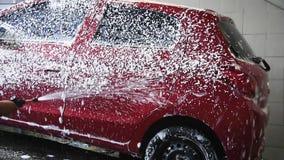 Lavagem do carro, bolha de sabão do pulverizador do homem no carro filme