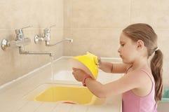 Lavagem elementar da idade da menina caucasiano pequena pratos exteriores Imagem de Stock Royalty Free