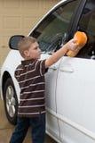 Lavaggio d'aiuto del ragazzino l'automobile di famiglia Immagine Stock