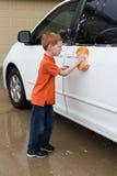 Lavaggio d'aiuto del ragazzino l'automobile di famiglia Fotografia Stock Libera da Diritti