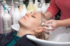 Lavaggio dei capelli ad un salone di lavoro di parrucchiere Immagini Stock