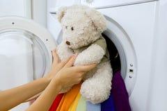 Lavaggio delicato: donna che prende giocattolo lanuginoso dalla lavatrice Fotografia Stock