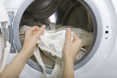 Lavaggio delicato, donna che prende lavanderia delicata (biancheria intima) dal wa Fotografie Stock