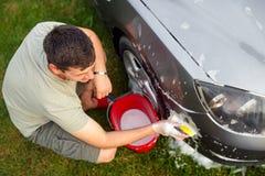 Lavaggio dell'automobile di vista superiore Automobile di pulizia facendo uso della spugna e della schiuma fotografia stock