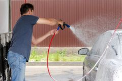 Lavaggio dell'automobile facendo uso dell'acqua ad alta pressione fotografia stock libera da diritti