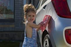 Lavaggio della bambina un'automobile Automobile pulita d'aiuto della famiglia del bambino Immagine Stock