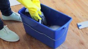 Lavaggio della donna e di spremuta in secchio straccio a casa video d archivio