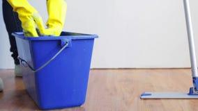 Lavaggio della donna e di spremuta in secchio straccio a casa stock footage