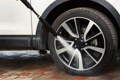 Lavaggio della ruota di automobile con la rondella ad alta pressione Fotografia Stock