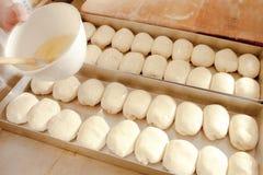 Lavaggio di spazzolatura dell'uovo su pasticceria Fotografie Stock