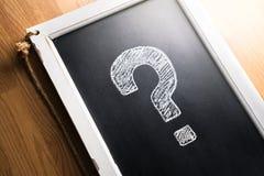 Lavagna attinta del punto interrogativo Circa noi, aiuto o informazioni per l'affare Concetto di indagine, di scrutinio o di quiz fotografia stock libera da diritti