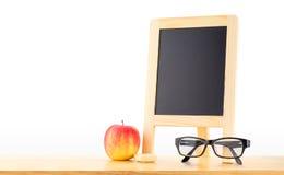 Lavagna in bianco con la mela rossa e vetri sulla tavola di legno al whi Fotografie Stock Libere da Diritti