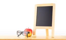 Lavagna in bianco con la mela rossa e vetri sulla tavola di legno al whi Fotografia Stock