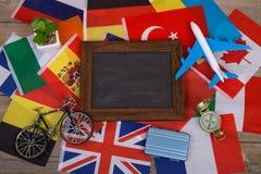 Lavagna in bianco del tempo di viaggio, bandiere dei paesi differenti, modello dell'aeroplano, poca bicicletta e valigia, bussola Immagini Stock Libere da Diritti