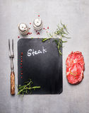 Lavagna che cucina fondo con bistecca, la forcella della carne, le erbe e le spezie crude, vista superiore Immagini Stock