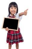 Lavagna cinese asiatica della tenuta della bambina con i pollici su Fotografie Stock Libere da Diritti